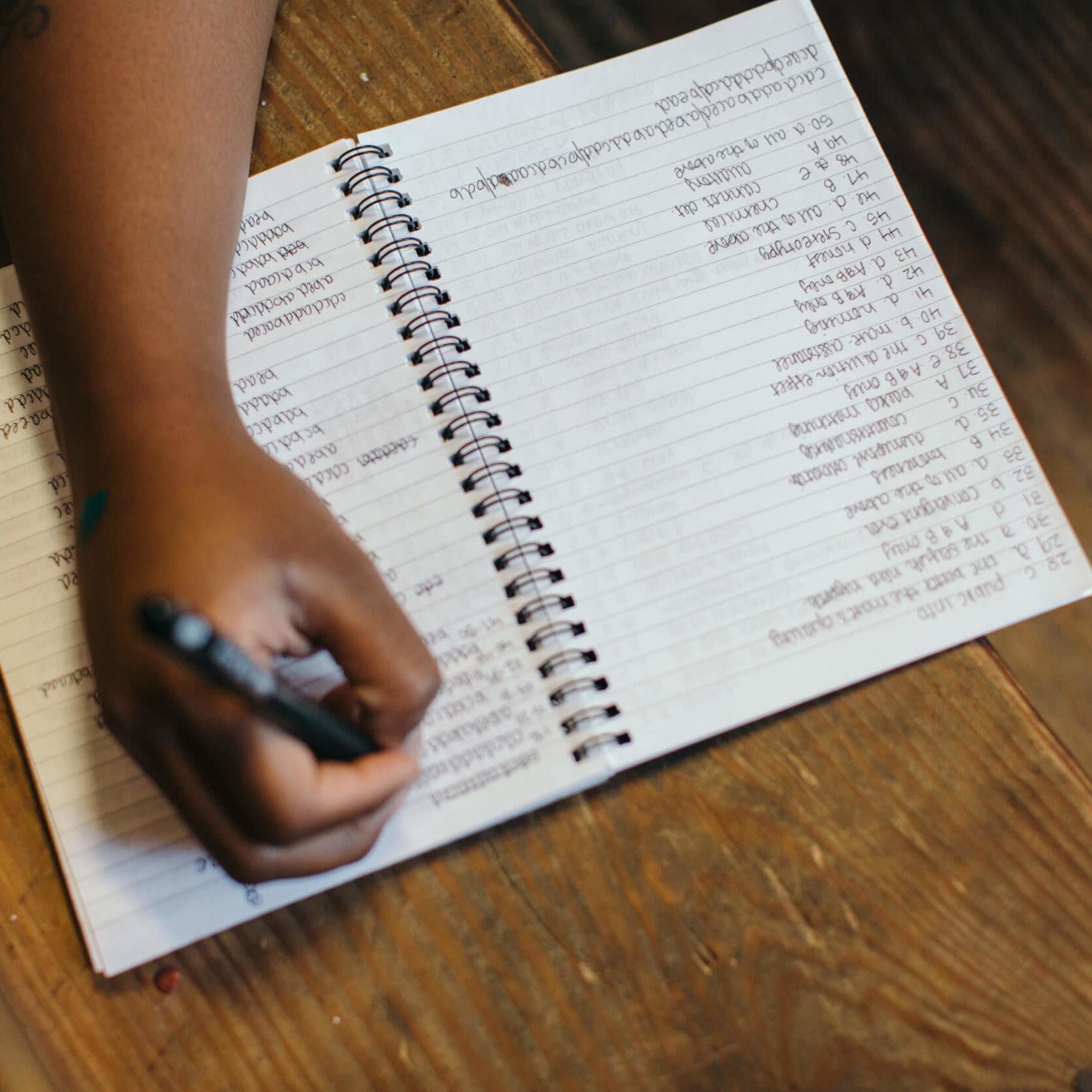 Persoon schrijft ideeën in een boekje. Om een goede merknaam te bedenken is het belangrijk er eerst zoveel mogelijk op te schrijven.