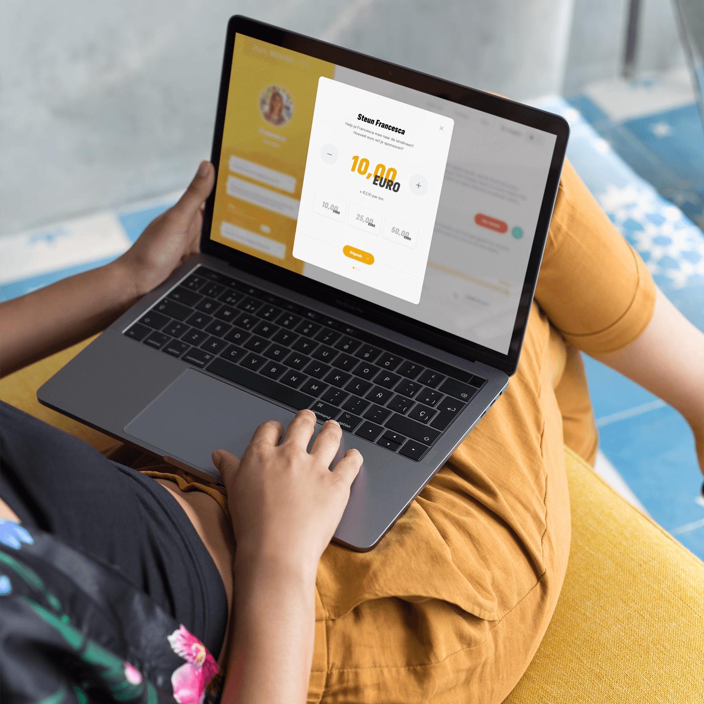 Een vrouw sponsort een deelnemer met een online betaling op het digitale platform van Moving lives